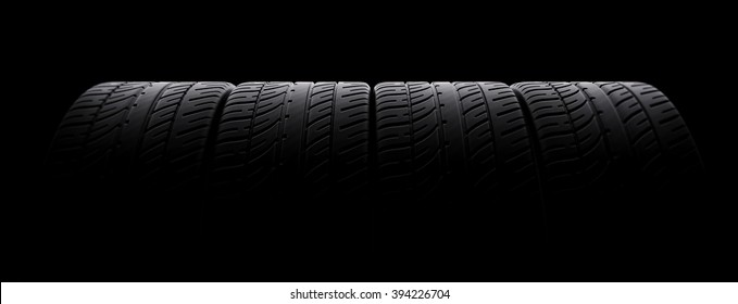 Tires in a row on black background