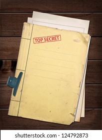top secret file on wooden table.
