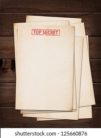 top secret files on wooden table.