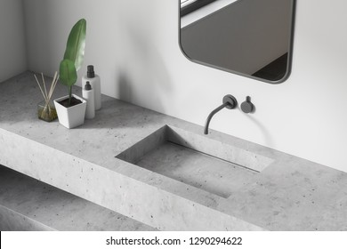 Top view of bathroom sink made of white stone with vertical mirror above it standing in room with white walls. 3d rendering