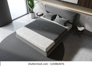 Top view of bedroom interior with gray and wooden walls, master bed standing on round carpet and concrete floor. 3d rendering