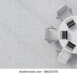 Top view of a half of the conference room. A white round table, three white leather chairs. Three laptops are on the table. Office interior. 3D rendering.