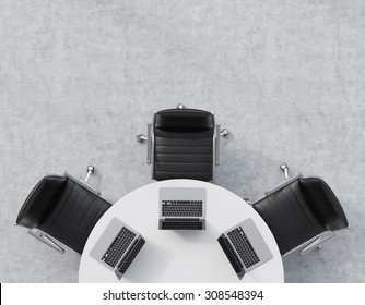Top view of a half of the conference room. A white round table, three black leather chairs. Three laptops are on the table. Office interior. 3D rendering.