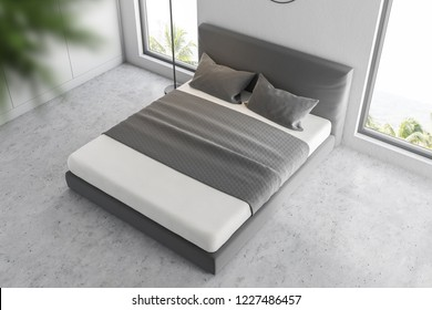 Top view of master bedroom interior with white walls, concrete floor and white and gray master bed in the center. 3d rendering