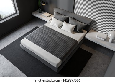 Top view of minimalistic bedroom with gray and wooden walls, concrete floor, gray master bed with white bedside tables and gray carpet. 3d rendering