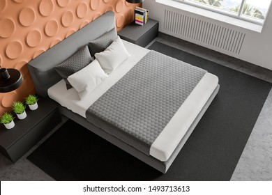 Top view of stylish bedroom with orange geometric pattern and white walls, concrete floor with carpet, king size bed and two gray bedside tables. 3d rendering