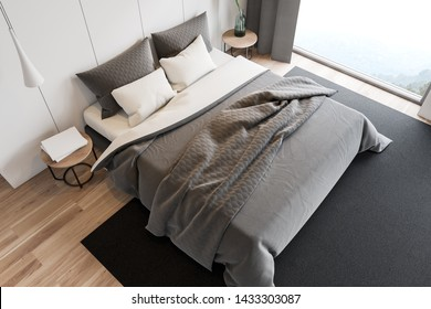 Top view of stylish master bedroom with white walls, wooden floor, double bed on gray carpet, two bedside tables with books and plant and large window with mountain view. 3d rendering