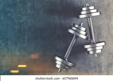 Top view of two shiny steel dumbbells lying on a concrete floor. They are casting shadows. Concept of a healthy lifestyle. 3d rendering mock up toned image