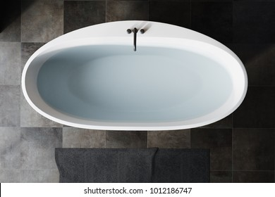 Top view of a white bath tub filled with clear water standing on a black tiled bathroom floor. 3d rendering