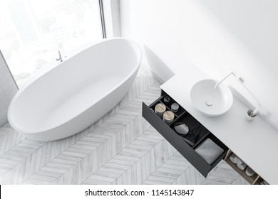 Top view of a white bathtub standing on the white wooden floor of a white wall room under the window. 3d rendering