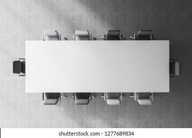 Top view of white meeting room table with gray and white chairs standing around it in room with concrete floor. 3d rendering