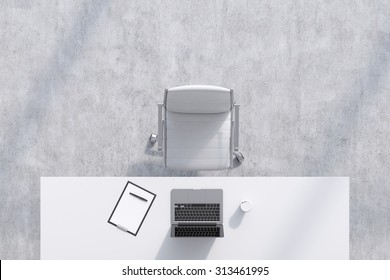 Top view of a workplace in a modern office. A white table, white leather chair. Laptop, writing pad for notes and a cup of coffee are on the table. Concrete floor. Office interior. 3D rendering.