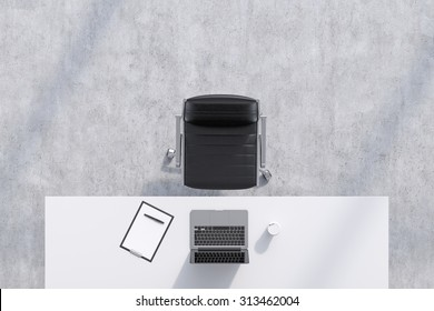 Top view of a workplace in a modern office. A white table, black leather chair. Laptop, writing pad for notes and a cup of coffee are on the table. Concrete floor. Office interior. 3D rendering.