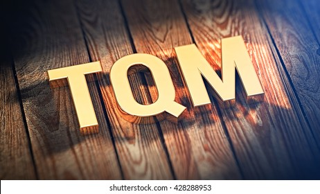 "Total Quality Management concept. Acronym ""TQM"" is lined with gold letters on wooden planks. 3D illustration image"