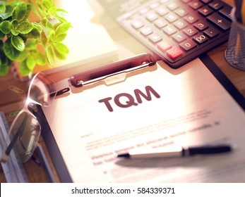 TQM on Clipboard. Office Desk with a Lot of Office Supplies. 3d Rendering. Blurred Toned Illustration.