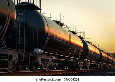 Transportation tank cars with oil during sunset.