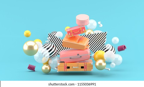 Travel bag overlaps among the colorful balls on the blue background.-3d rendering.