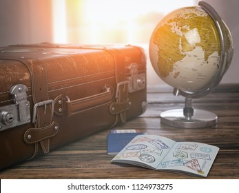 Travel or turism concept.  Old  suitcase  with open passport with visa stamps and globe. 3d illustration
