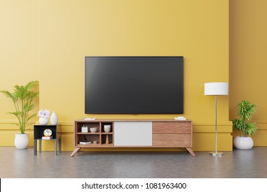 TV on cabinet  in modern living room with lamp,table,flower and plant on yellow wall background,3d rendering