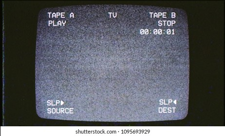 A tv screen showing noise from an old VHS tape tracking a bad signal. Double deck layout. Cool retro vintage background.