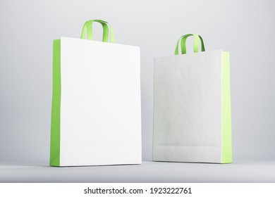 Two blank white and green recycled paper bags with space for your sign. Mockup. 3D rendering