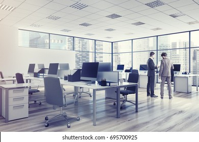 Two businessmen aare talking in an open space office environment with rows of computer desks and loft windows. Corner. 3d rendering mock up toned image