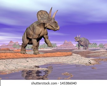 Two diceratops dinosaurs next to water in colorful rocky landscape by cloudy day
