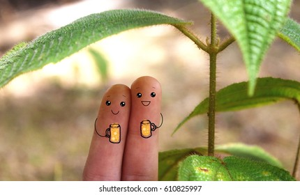Two fingers decorated as sweet couple or friends drinking beer under a tree.