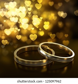 Two golden wedding rings with heart bokeh on background