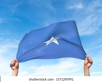 Two hands are holding a Somalia flag - flowing through the wind. 3D Illustration.
