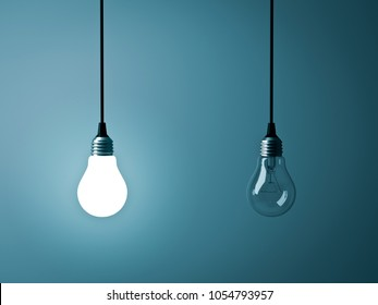 Two hanging light bulbs , One glowing and one turned off on dark green blue background . 3D rendering.