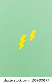 Two lightning bolts cut from yellow paper on green background