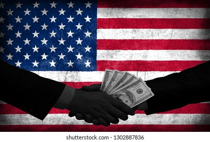 Two men/politicians in suits holding money/US Dollars and shaking hands with the national flag on the background - United States