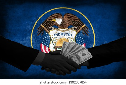 Two men/politicians in suits holding money/US Dollars and shaking hands with the national flag on the background - Utah - United States