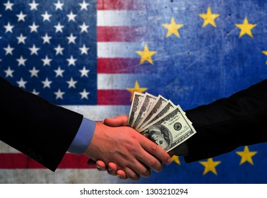 Two men/politicians in suits holding money/US Dollars and shaking hands with the national flag on the background - United States of America and European Union