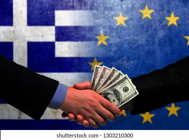 Two men/politicians in suits holding money/US Dollars and shaking hands with the national flag on the background - Greece and European Union
