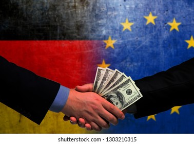 Two men/politicians in suits holding money/US Dollars and shaking hands with the national flag on the background - Germany and European Union