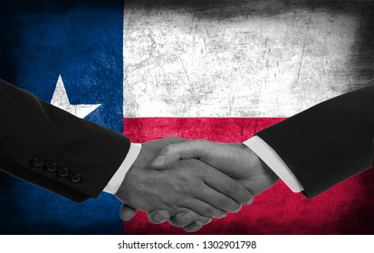 Two men/politicians in suits shaking hands with the national flag on the background - Texas - United States