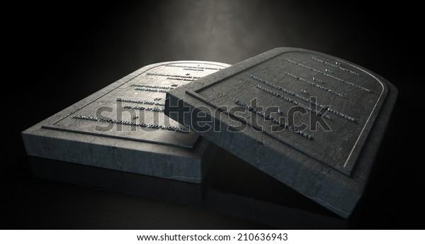 Deux tablettes de pierre représentatives avec les dix commandements inscrits sur elles sur fond noir et éthéré isolé