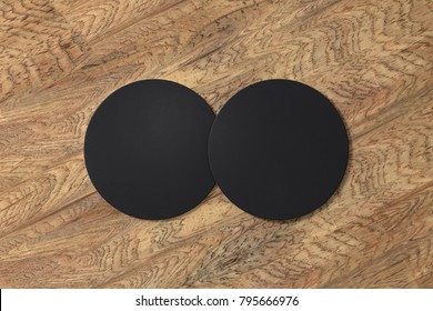 Two round black coasters on wood background. 3d illustration
