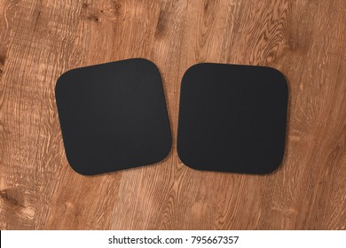 Two square black coasters on wood background. 3d illustration
