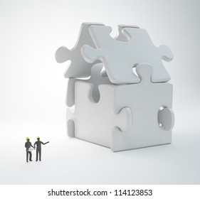 Two tiny people engineers building a puzzle house