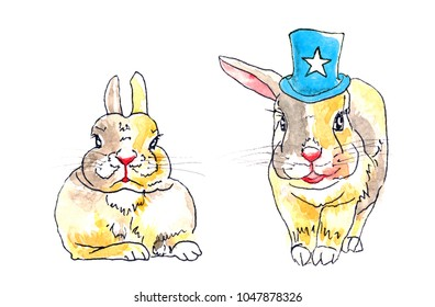 Two yellowish dwarf rabbits: one is wearing a blue hat with a star, the other is lying with its ears up.
