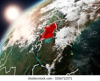 Uganda during sunset highlighted in red on planet Earth with clouds and visible country borders. 3D illustration. Elements of this image furnished by NASA.