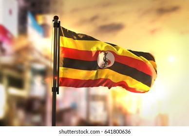 Uganda Flag Against City Blurred Background At Sunrise Backlight 3D Rendering