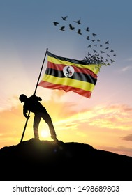 Uganda flag turn to birds while being planted by a man on a hill during sunrise.