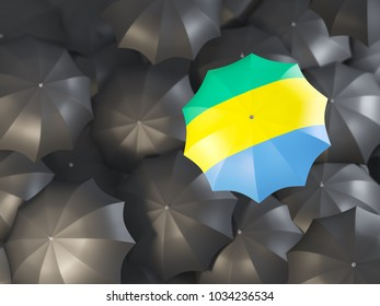 Umbrella with flag of gabon on top of black umbrellas. 3D illustration