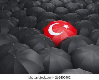 Umbrella with flag of turkey over black umbrellas
