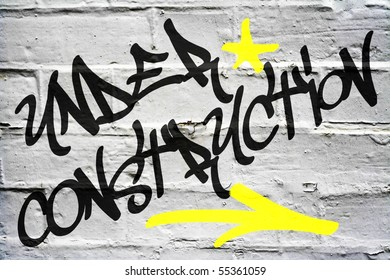 Under Construction Graffiti on White Brick Wall
