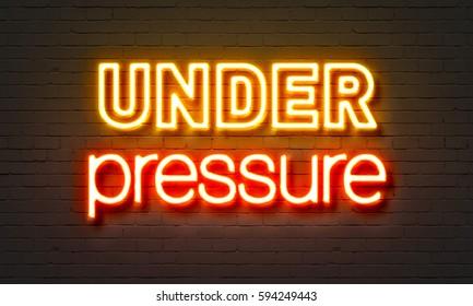 Under pressure neon sign on brick wall background